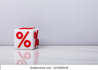 White Cubic Block With Red Percentage Sign On Reflective Desk