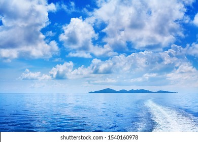 White cumulus clouds in blue sky over sea landscape, many clouds above ocean water panorama, ship trail, island on horizon line, beautiful tropical sunny summer seascape panoramic view, cloudy weather