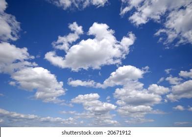 White cumulus clouds and a blue sky.