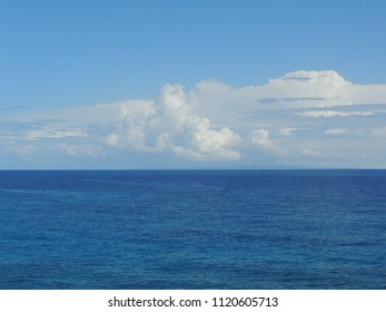 White cumulus clouds over the blue waters of the Pacific Ocean with the islands of Molokai and Lanai in the distance as seen from the Halona Blowhole Lookout in Oahu, Hawaii