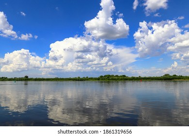 White cumulus clouds are reflected in the Neman river. Kaliningrad region and Lithuania