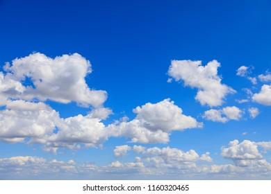 White cumulus summer clouds against a deep blue sky.