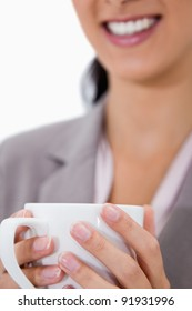 White cup being held by female hands against a white background