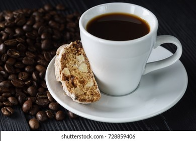 White cup with biscotti or cantucci, traditional Italian biscuit. Coffee beens on black rustic