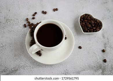White cup with black coffee and coffee beans on a concrete. Soft focus.