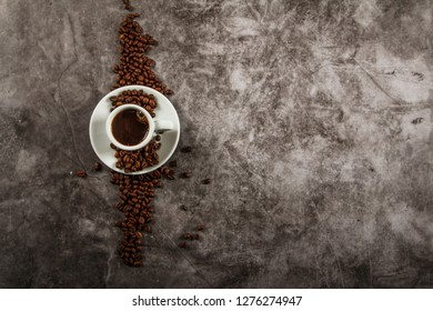 White cup with black coffee and grains of coffee on a background of gray stone. View from above. Place for text.