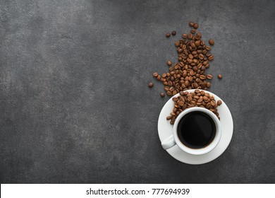 white cup with black coffee and roasted beans on stone background