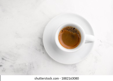 White cup of black espresso coffee on white textured marble background. Close-up shot, top view.