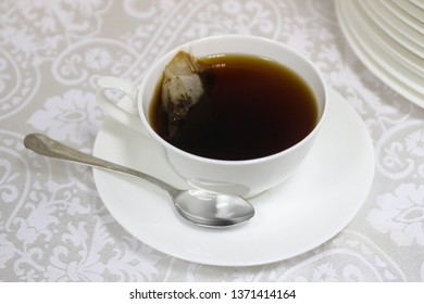 White cup with black tea and a spoon on a white tablecloth