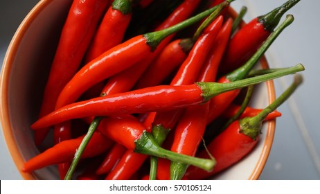 The white cup or bowl of very red chilies with their green head branches, put on the white grey table, ready to be ingredient of hot and spicy traditional food for cooking by gourmet chef