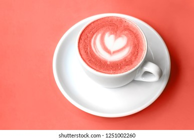 White cup of cappuccino with beautiful latte art on a table. Place for text. Shallow depth of field with focus. Color of the year 2019. Living coral.