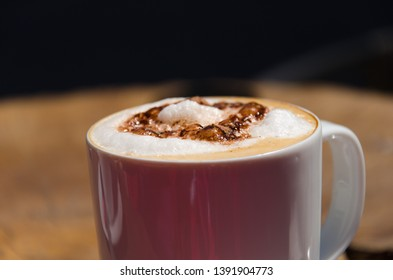 White cup of cappuccino with brown foam on blurred background