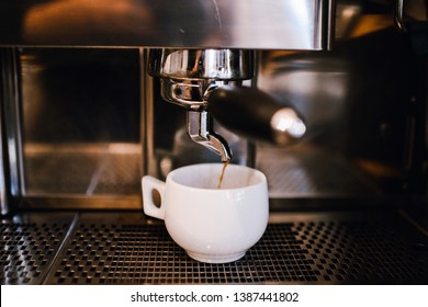 White cup of cappuccino. Industrial coffe machine. The process of making coffee step by step. Coffee shop, cafe, bar.