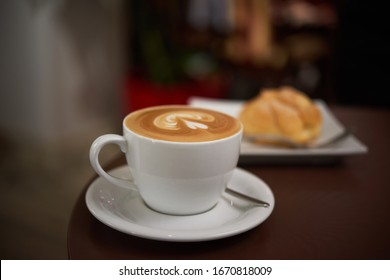 white cup with cappuccino on a brown table, selective focus