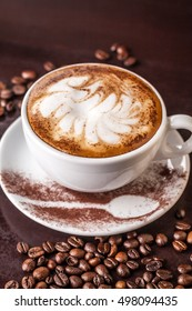 white cup of cappuccino on an old wooden table, coffee beans scattered on the table