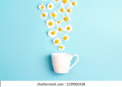 White cup and chamomile flowers on a blue background. Chamomiles come out of the cup like steam. Chamomile tea concept. Flat lay, top view.