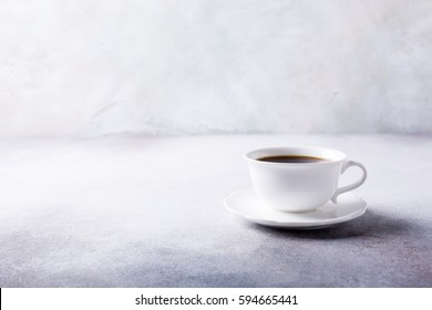 White cup of coffee with amaretti cookies on light gray background with copy space.