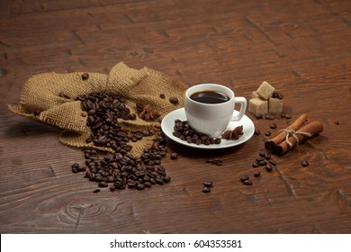 White cup of coffee with coffee beans, cinnamon, star anise on old wooden table.