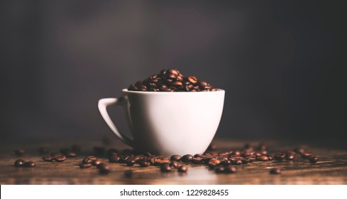 White cup of coffee beans isolated on wooden table. Coffee drink. Coffee lovers. Caffeine.