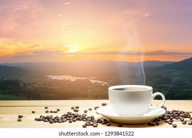 White cup of coffee and coffee beans on wood table with sunset background natural