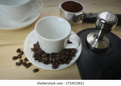 White cup with coffee beans placed in the coaster