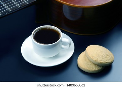 white cup with coffee and biscuits in the background acoustic guitar. hot drink