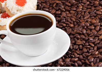 white cup of coffee and cookies on beans