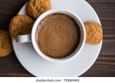White cup of coffee and cookies on the wooden table