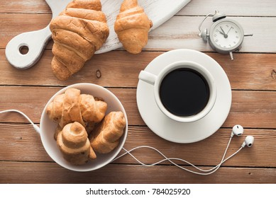 white cup of coffee with croissant, alarm clock and music headphones on a wood table. top view. cheerful start to the day
