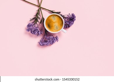 White cup of coffee and flowers on isolated pink desk. Flat lay, top view, copy space.