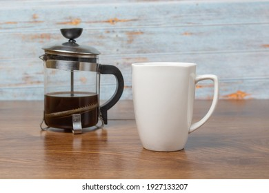white cup of coffee and french press with coffee on wooden boards