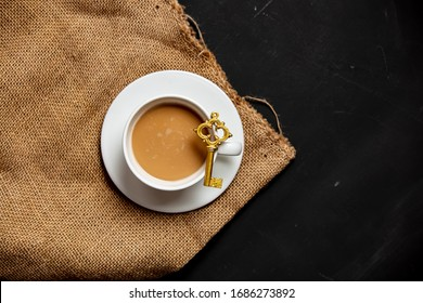 White cup of coffee and golden key on dark background