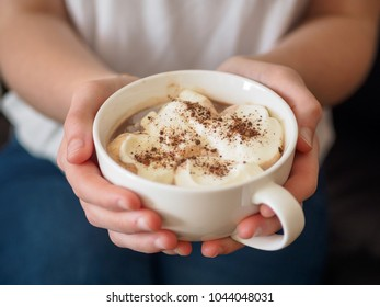 A white cup of coffee in the hands of a young girl. Close-up name on a cup. Blue jeans and white T-shirt.