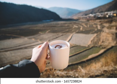 A white cup of coffee in man's hand with view of fields farm and mountains at coffee shop in Paro, Bhutan.