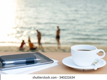 White cup of coffee and mobile smart phone tablet on table at the beach in the morning.