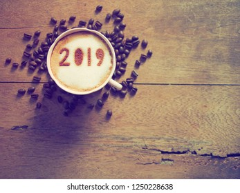 White cup of coffee with the number 2019 over frothy surface on wooden background with coffee beans. Holidays food art concept for active days in New Year, Welcome 2019. (top view, space for text)