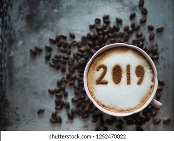White cup of coffee with the number 2019 on frothy surface on grey cement background with coffee beans. Holidays food art concept for active days in New Year, Welcome 2019. (top view, space for text)