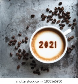 White cup with coffee and number 2021 over frothy surface serving in rustic aluminum tray with coffee beans and space for text. New year new you, Holidays food art theme Happy New Year 2021. (square)