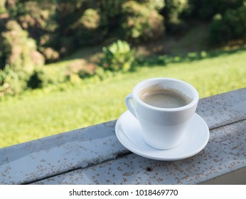 White cup of coffee on bar. Beauty nature background of tea plantation at Doi-Montngo , Chiang Mai, Thailand