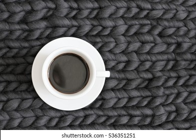 White cup of coffee on dark grey super chunky knitted blanket. Top view point.