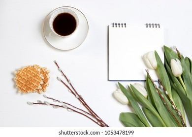 white cup of coffee on a white notebook , white tulips, a willow branch on a white wooden table. Copy space