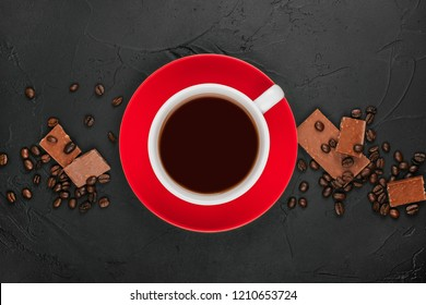 White cup of coffee on the red plate with roasted coffee beans and milk chocolate on the black concrete stone background. Flatlay style.