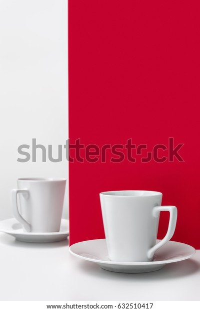 A white cup of coffee on a red and white background, with space for text and advertising.
