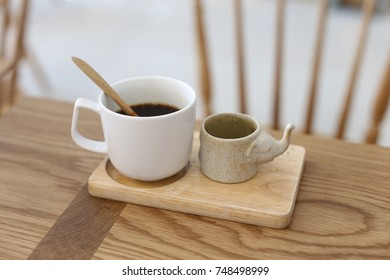 white cup coffee on wood dish and table