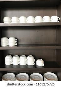 white cup of coffee on wooden shelf.