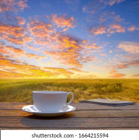 A white cup of coffee on wooden table beside golden field in the evening summer sunset.