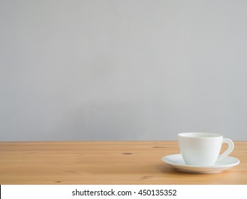 White cup of coffee on wooden table.