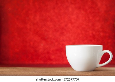 White cup of coffee on wooden table with red bokeh background, valentine's day and romance concept