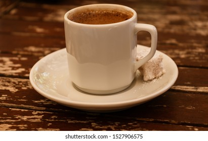 a white cup of coffee and a peace of a turkish delight (rahat lokum) on wooden table