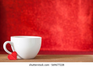 White cup of coffee with red heart paper origami on wooden table with red bokeh background, valentine's day and romance concept